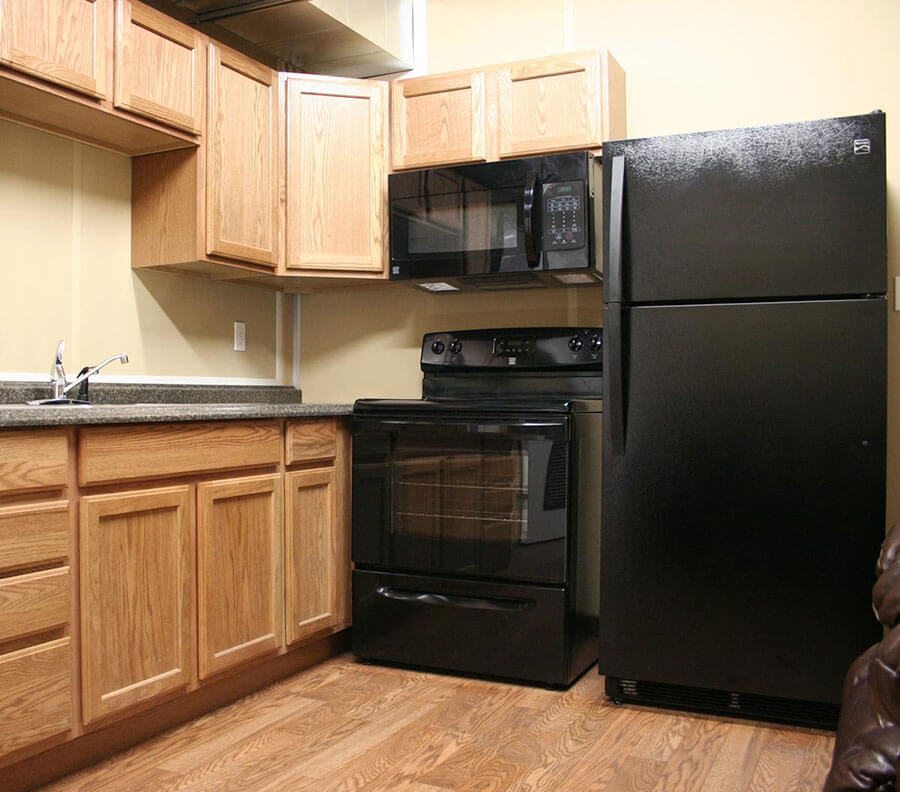 Kitchens include fitted cupboards and appliances.